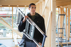 Carpenter Carrying Ladder At Construction Site Royalty Free Stock Images