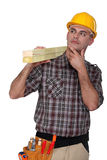 Carpenter carrying lumber Royalty Free Stock Photos