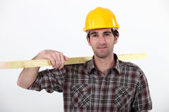 A carpenter carrying a plank. Royalty Free Stock Photography