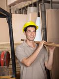 Carpenter Carrying Plank While Looking Away Royalty Free Stock Photos