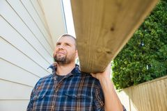 Carpenter Carrying Plank On Shoulder At Royalty Free Stock Images