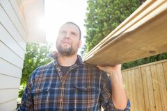 Carpenter Carrying Planks While Looking Away At Royalty Free Stock Photography