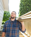 Carpenter Carrying Planks On Shoulder At Royalty Free Stock Photo