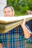 Carpenter Carrying Wooden Planks Outdoors Royalty Free Stock Photos