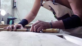 A carpenter carves a wooden part with dovetail elements using a chisel.woodworker makes a dovetail joint for a wooden part in a. Carpentry workshop. 4k. 4k stock footage