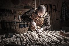 Carpenter carving wood. Caucasian carpenter carving wood in his workshop stock photography