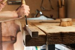 Carpenter carving wood with a chisel royalty free stock image