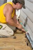 Carpenter Caulking. A carpenter caulking on a deck patio Stock Photos