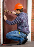 Carpenter changing lock in heavy metal door stock images