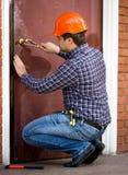 Carpenter changing lock in heavy metal door Stock Images