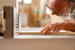 Carpenter checking board on a wood shaper Royalty Free Stock Photography