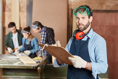 Carpenter with checklist. During organization and planning Royalty Free Stock Image