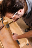 Carpenter with chisel and hammer Royalty Free Stock Images