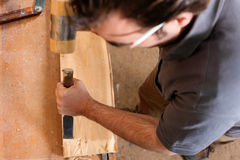 Carpenter with chisel and hammer Stock Photo
