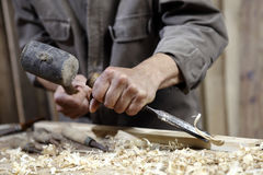 Carpenter with chisel in the hands on workbench in carpentry Stock Photo