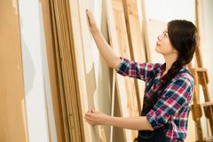 Carpenter choosing best wood board. Carpenter testing wood plank evenness and choosing best wood board at workshop. mixed race asian chinese model Stock Images