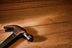 Carpenter Claw Hammer Tool on Oak Wood Boards. Carpenter claw hammer tool on oak wood workbench boards in a carpentry construction workshop Royalty Free Stock Photography