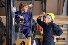 Carpenter Communicating With Colleague Using. Happy senior carpenter communicating with colleague using forklift in workshop Stock Photography