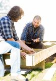 Carpenter Communicating With Coworker Measuring. Mid adult carpenter communicating with coworker measuring wooden frame at construction site Royalty Free Stock Images