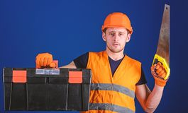 Carpenter concept. Man in helmet, hard hat carries toolbox and holds handsaw, blue background. Worker, repairer. Repairman on serious face carries toolbox stock photo