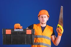 Carpenter concept. Worker, repairer, repairman on serious face carries toolbox, ready for repair, copy space. Man in. Helmet, hard hat carries toolbox and holds royalty free stock photography