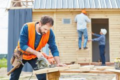 Carpenter at construction site. Cutting wood with circular saw royalty free stock image