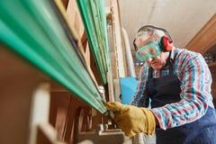 Carpenter controling vertical saw. Senior citizen as carpenter controling vertical saw Stock Image