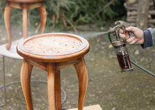 Carpenter is covering stool by lacquer. Furniture varnishing using sprayer (pulverizer Stock Image