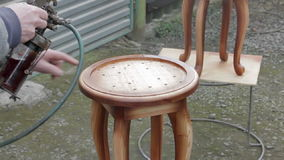 Carpenter is covering stool by lacquer. Furniture varnishing using sprayer (pulverizer stock video