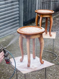 Carpenter is covering stool by lacquer. Furniture varnishing using sprayer or pulverizer Stock Images