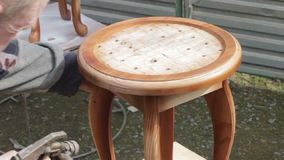 Carpenter is covering stool by lacquer. Furniture varnishing using sprayer (pulverizer). Furniture making stock footage