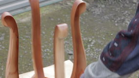 Carpenter is covering stool by lacquer. Furniture varnishing using sprayer (pulverizer). Furniture making stock video