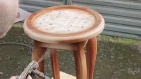 Carpenter is covering stool by lacquer. Furniture varnishing using sprayer (pulverizer). Furniture making stock video footage