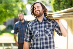Carpenter With Coworker Carrying Planks While Royalty Free Stock Photography