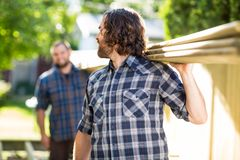 Carpenter And Coworker Carrying Wooden Planks Stock Photo