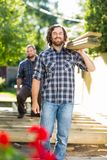 Carpenter And Coworker Carrying Wooden Planks At. Portrait of mid adult carpenter and coworker carrying wooden planks at construction site Stock Images