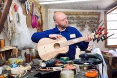 Carpenter creating guitar in workshop Royalty Free Stock Image