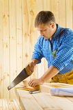 Carpenter cuts the plank. Yuong carpenter cuts the plank in the room royalty free stock image