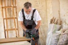 Carpenter cuts plywood with circular saw Royalty Free Stock Photo