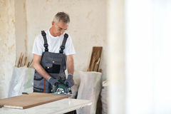 Carpenter cuts plywood with circular saw Royalty Free Stock Photography