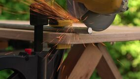 A carpenter cuts a steel rod with an electric hammer on workbench. Macro. A narrow zone of sharpness.