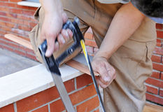 Carpenter cutting an aluminum profile with handsaw Royalty Free Stock Image