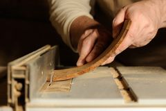 Carpenter cutting curved piece of wood by wood cutter. Closeup Royalty Free Stock Photo