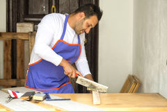 Carpenter cutting with handsaw Royalty Free Stock Images