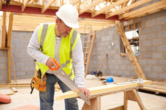 Carpenter Cutting House Roof Supports On Building Site Stock Photo