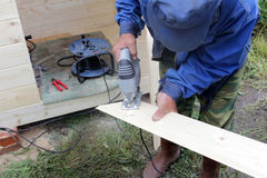 Carpenter cutting with a jigsaw plate. Royalty Free Stock Photos