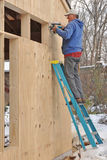 Carpenter cutting openings for windows. Carpenter cutting openings in plywood sheathing for windows stock image