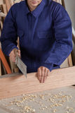 Carpenter cutting a piece of wood Royalty Free Stock Images