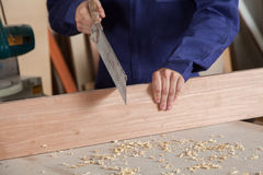 Carpenter cutting a piece of wood Royalty Free Stock Image