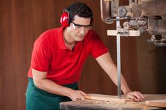 Carpenter Cutting Plank With Bandsaw Royalty Free Stock Photography